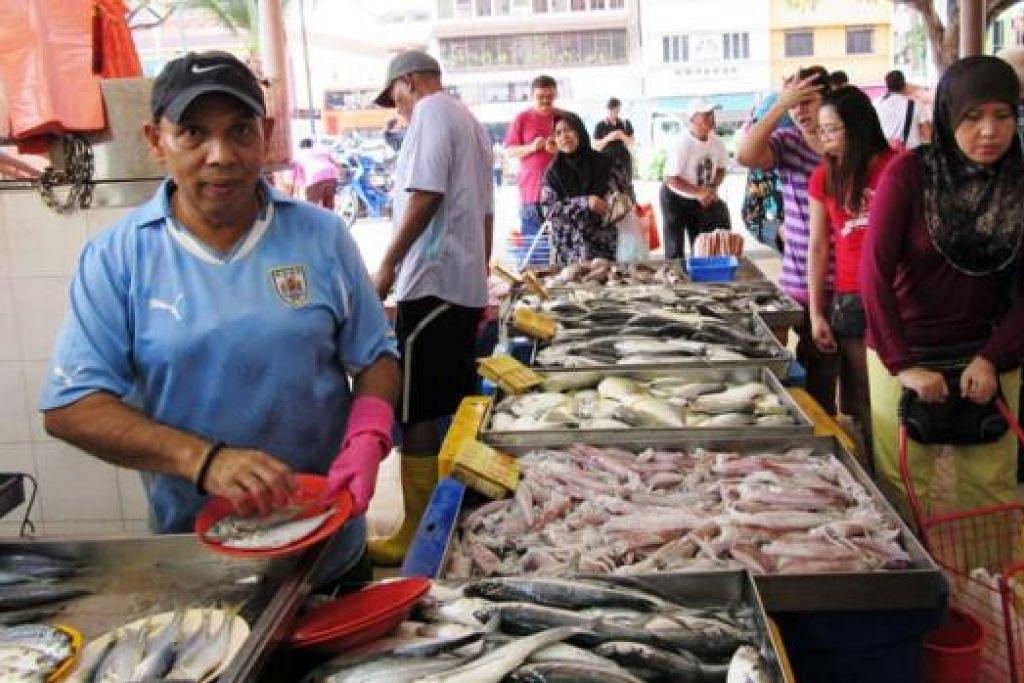 RAJA BUNGA CARI REZEKI JUAL IKAN: Encik Mohamad Arshad menjaja ikan di Pasar Geylang Serai sejak cuti sakit tanpa gaji lima bulan lalu hingga sekarang. - Foto SAINI SALLEH