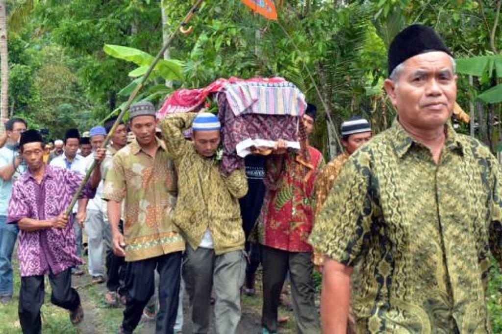 MANGSA PEMBUNUHAN KEJAM: Saudara-mara dan penduduk kampung Gandrungmangu di Cilacap mengiringi jenazah Allahyarhamha Sumarti Ningsih untuk dikebumikan kelmarin. - Foto AFP
