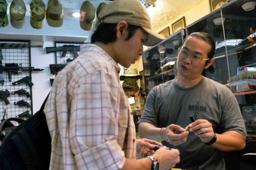 MESRA PELANGGAN: Pemilik kedai A.I.M. Spec, Encik James Quek (kanan), sedang memberi penerangan kepada pelanggannya tentang cara menggunakan lampu suluh. - Foto-foto KHALID BABA