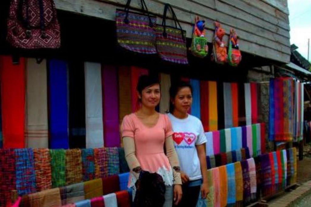 HASIL KRAF TANGAN: Dua gadis jurujual ini menjual barang tenunan di kampung Ban Xang Hai dekat Tebing Sungai Mekong. - Foto-foto MOKSIM SALEH