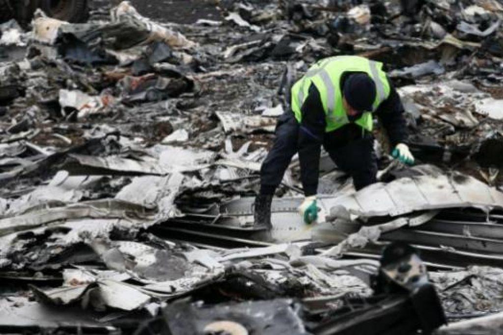 KAWASAN NAHAS: Seorang penyiasat Belanda memeriksa bangkai pesawat MH17 dekat perkampungan Hrabove, timur Ukraine. - Foto REUTERS