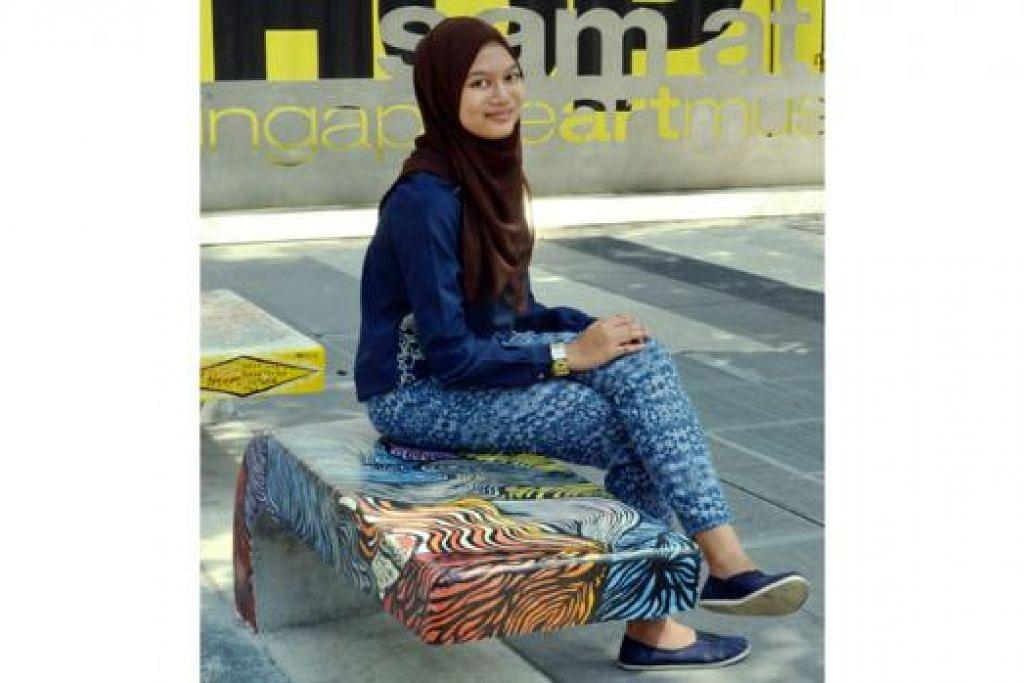 LUKISAN SPONTAN: Cik Nur Syuhada Ahmad Soribah gembira kesungguhannya memalit lorekan dan lengkungan cat yang tampak 'seksi' pada bangku ini dihargai.
