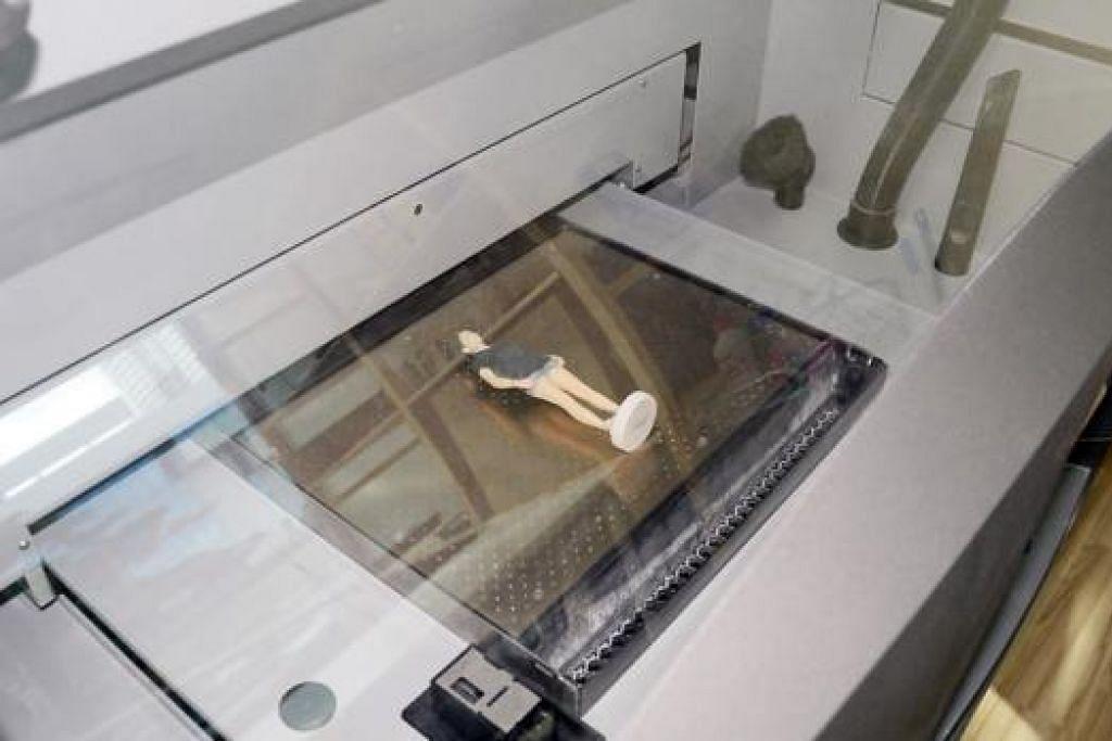 HAMPIR SIAP: Mesin percetakan tiga dimensi hampir selesai menghasilkan patung kenit manusia.