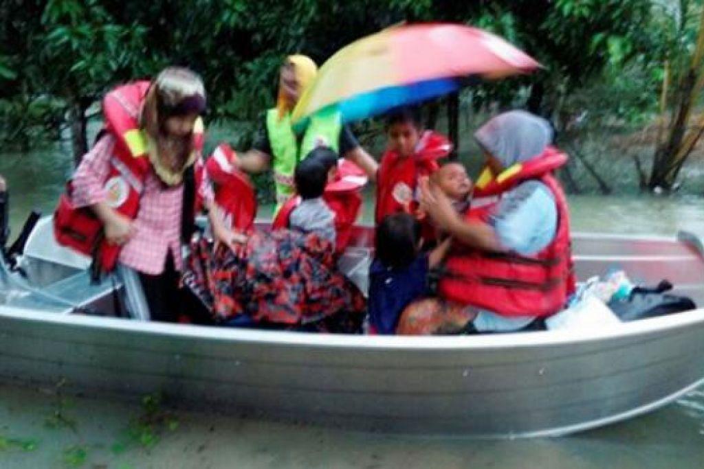 DIPINDAHKAN AKIBAT BANJIR: Penduduk Kampung Tasek, Bukit Awang di Kuala Terengganu dipindahkan ke pusat pemindahan banjir sementara di Sekolah Kebangsaan Wakaf Raja dengan bantuan anggota Bomba dan Penyelamat Pasir Putih. - Foto BHM