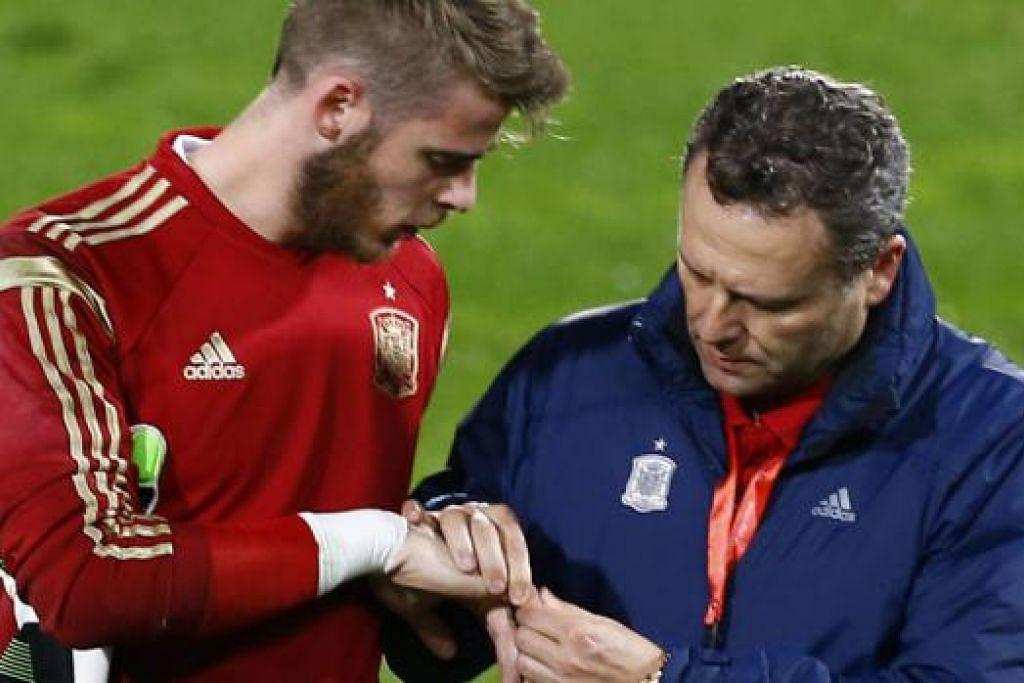 TIDAK DAPAT BERAKSI: Penjaga gawang Manchester United, David de Gea (kiri), mendapatkan kepastian daripada doktor atas kecederaan yang dialaminya sewaktu berlatih dengan pasukan Sepanyol minggu lalu. - Foto REUTERS