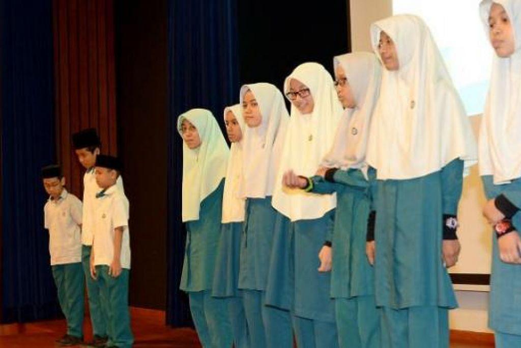 CEMERLANG: Aisyah Nurul Izza (empat dari kiri) muncul sebagai pelajar madrasah terbaik PSLE sejauh ini dengan agregat 269 mata. - Foto TUKIMAN WARJI