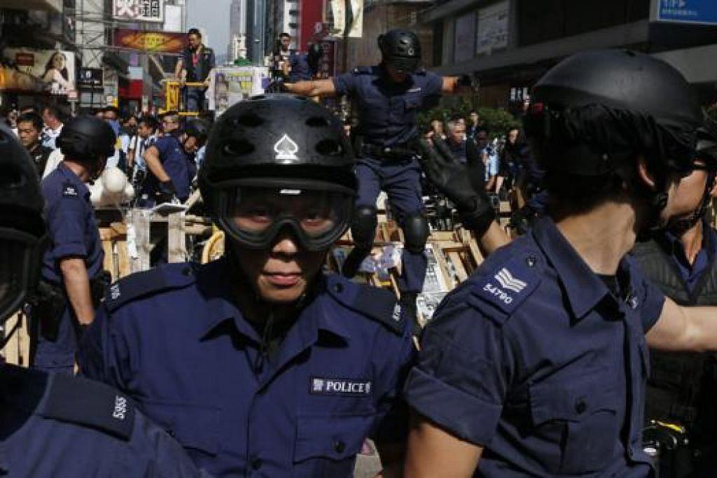 ALIHKAN PENGADANG: Pegawai polis semalam mengalihkan pengadang di jalan raya Nathan Road semalam. - Foto REUTERS