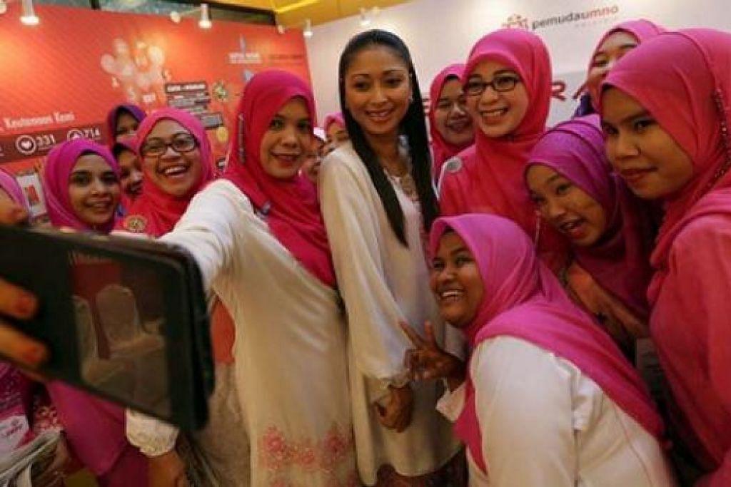 SEMPAT AMBIK SELFIE: Beberapa perwakilan Puteri Umno mengambil selfie sewaktu Perhimpunan Agung Umno semalam, yang berkisar tentang penakatan Barisan Nasional dalam pilihan raya umum akan datang. - Foto BHM