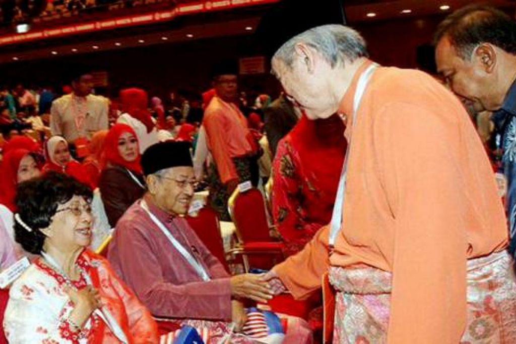 BERJABAT MESRA: Dr Mahathir (duduk) menyambut salaman Tun Abdullah di Perhimpunan Agung Umno semalam. - Foto BHM