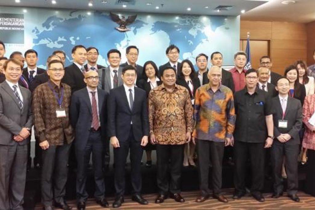 KUKUH JALINAN: Encik Teo (depan, empat dari kiri) bersama Menteri Perdagangan Indonesia, Encik Rachmat Gobel (sebelah kiri Encik Teo dan berbaju batik), bergambar bersama para anggota misi dagangan dari Singapura. - Foto IE SINGAPORE