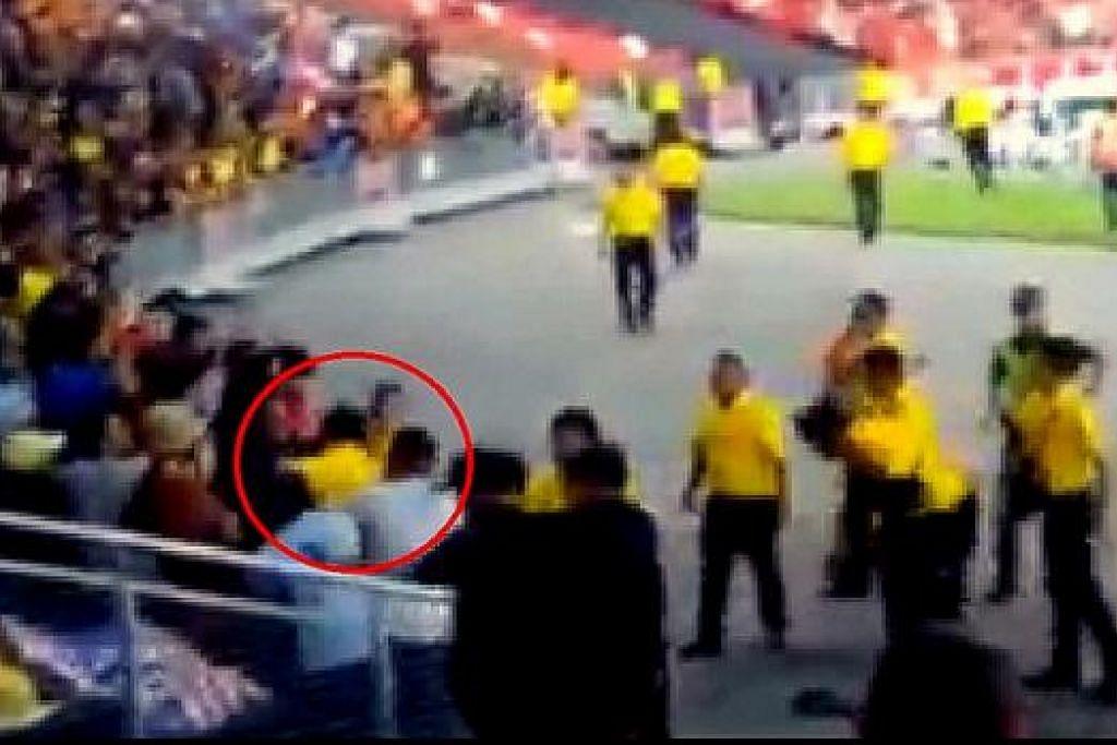 KEADAAN CEMAS: Pegawai keselamatan dalam bulatan merah dikerumuni sekumpulan penyokong sebaik sahaja beliau memasuki kawasan penyokong. - Foto INTERNET