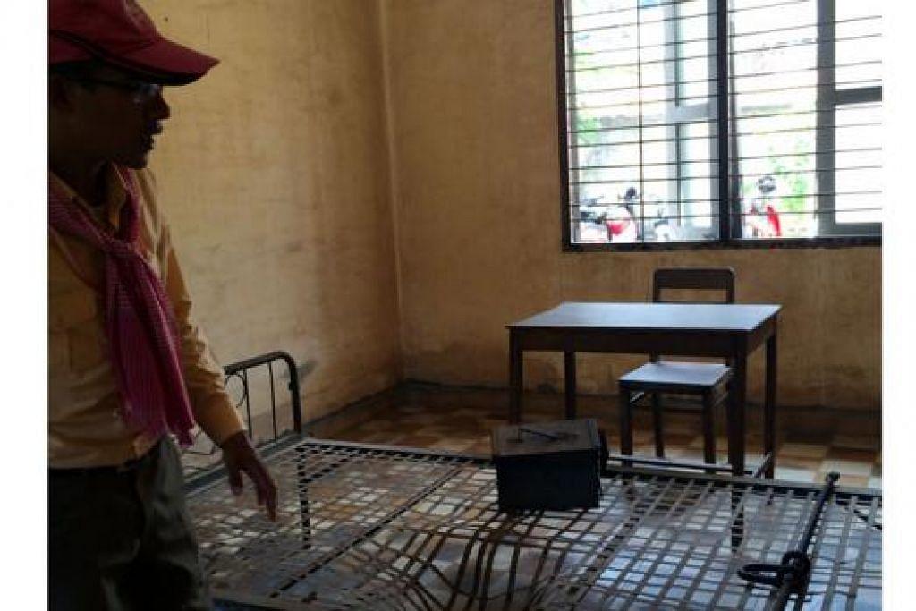 BILIK PENYEKSAAN: Pemandu pelancong, Encik Rahman, menunjukkan sebuah bilik di mana tahanan pernah diseksa dengan pelbagai cara seperti dikenakan kejutan elektrik, kuku mereka dicabut atau tubuh mereka dikelar dengan pisau di penjara di Tuol Sleng, Phnom Penh, semasa zaman pemerintahan Khmer Rouge dari 1975 hingga 1979. - Foto-foto DEWANI ABBAS