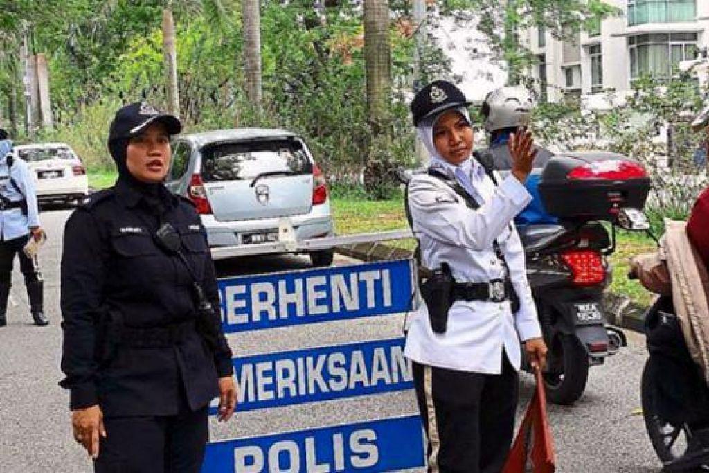 PENDEKATAN LEMBUT: Polis trafik menggunakan pendekatan lebih 'lembut' dengan melaksanakan sekatan jalan raya yang dijaga pegawai polis wanita. - Foto THE STAR