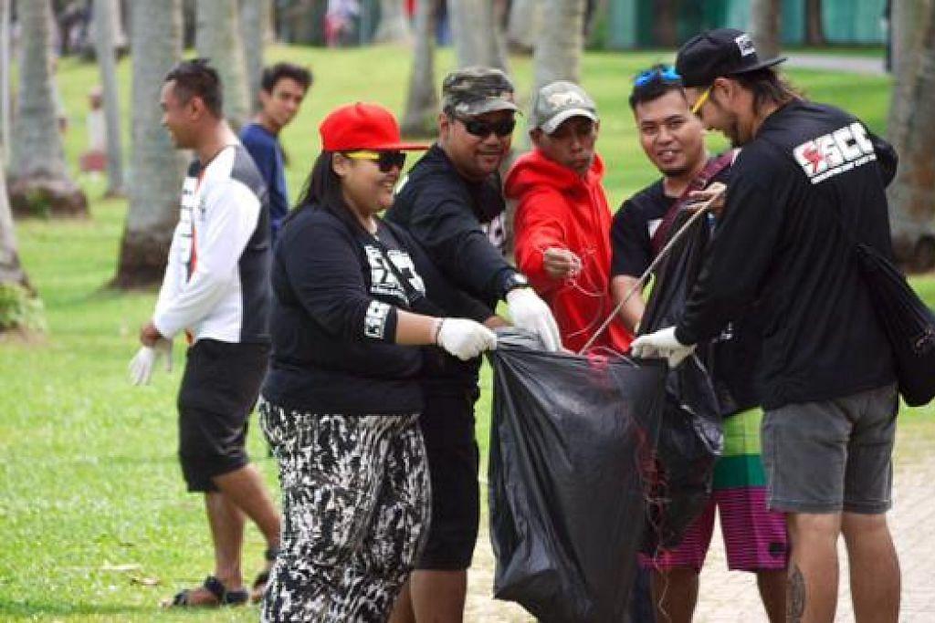 BERTANGGUNGJAWAB: Kaki pancing membersihkan pantai Pasir Ris Park menjelang pertandingan memancing esok. - Foto FISHINGKAKI.COM