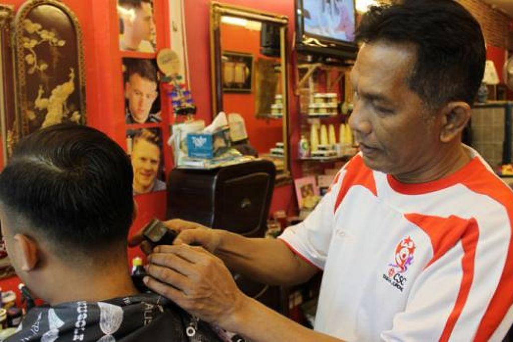 BELAJAR STAIL RAMBUT BARU: Encik Adris Osnam, pemilik Hj Osnam Malay Barber Shop, sanggup mempelajari stail rambut yang popular sekarang demi memenuhi permintaan pelanggan muda. - Foto SITI AISYAH NORDIN
