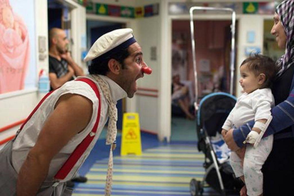 MENGHIBURKAN KANAK-KANAK: Seorang doktor badut dilihat sedang menghiburkan seorang kanak-kanak di sebuah hospital di Baitulmakdis. - Foto WWW.ZIMBIO.COM