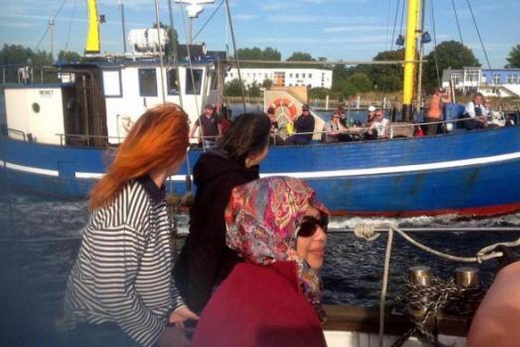 NIKMATI PEMANDANGAN DI SUNGAI: Penulis (bertudung) bersiar-siar dari Sungei Warnow di Rostock melalui Warnemunde, dalam perjalanan ke Laut Baltic. - Foto-foto ihsan SITI RAHIMAH MOHAMAD