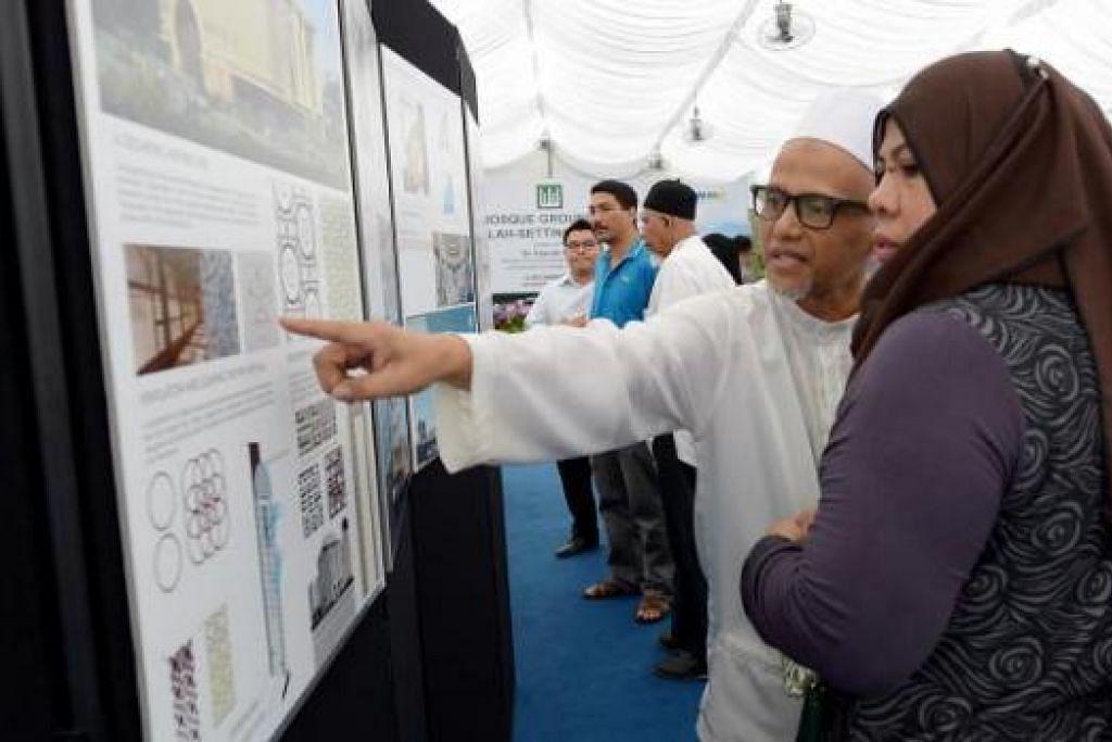 KONGSI PERIHAL REKA BENTUK MASJID: Pengunjung majlis pembetonan Masjid Maarof menyaksikan pameran yang antara lain mengetengahkan reka bentuk masjid apabila siap menjelang akhir 2016.