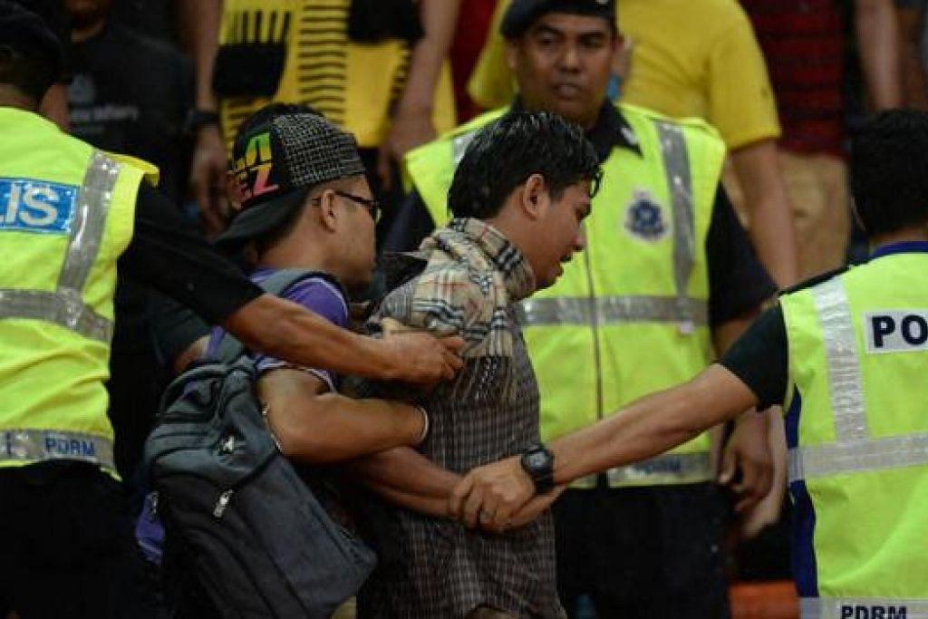 ANGKARA PERBUATAN LIAR: Seorang penyokong diberkas polis kerana terlibat dalam keganasan yang berlaku di Stadium Shah Alam Ahad lalu. Encik Khairy berharap pesalah lain akan segera diberkas polis. - Foto AFP