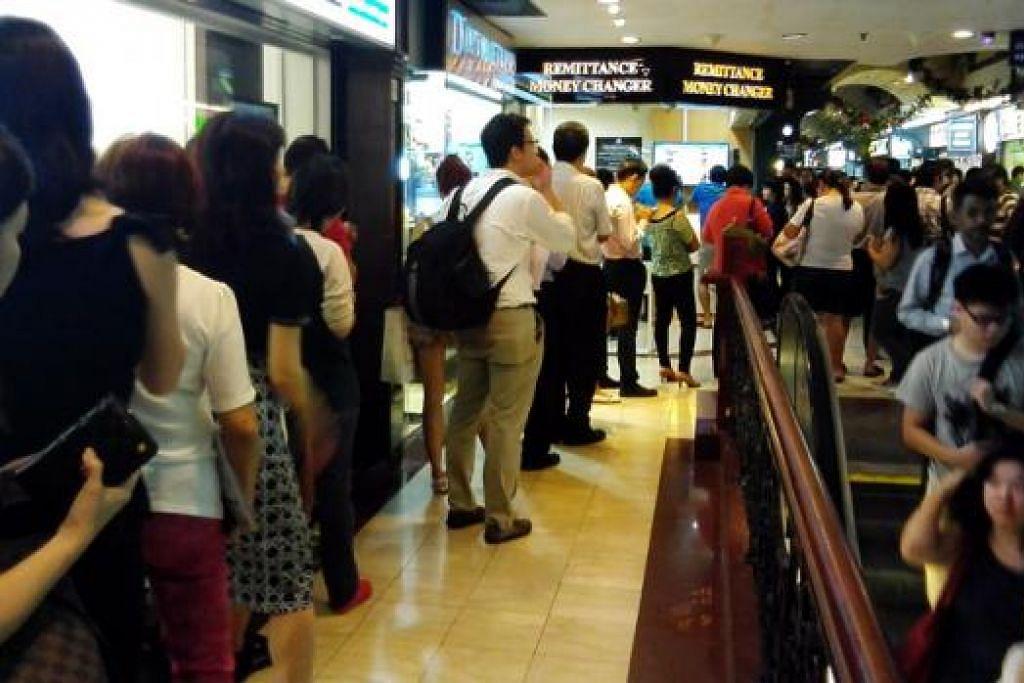 RINGGIT JATUH: Orang ramai tidak melepaskan peluang menukar dolar Singapura ke ringgit Malaysia (RM) semalam apabila nilai mata wang RM turun lagi minggu ini. - Foto A. RAHMAN BASRUN