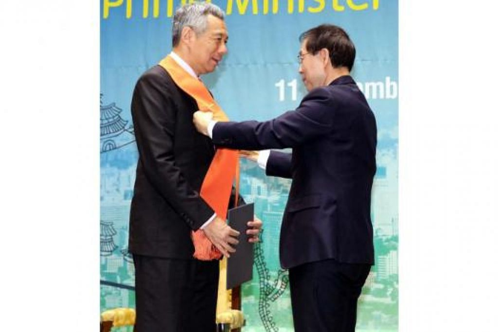 ERAT IKATAN: PM Lee menerima anugerah Warga Kehormat Seoul daripada Mayor Park Won-soo. - Foto MCI