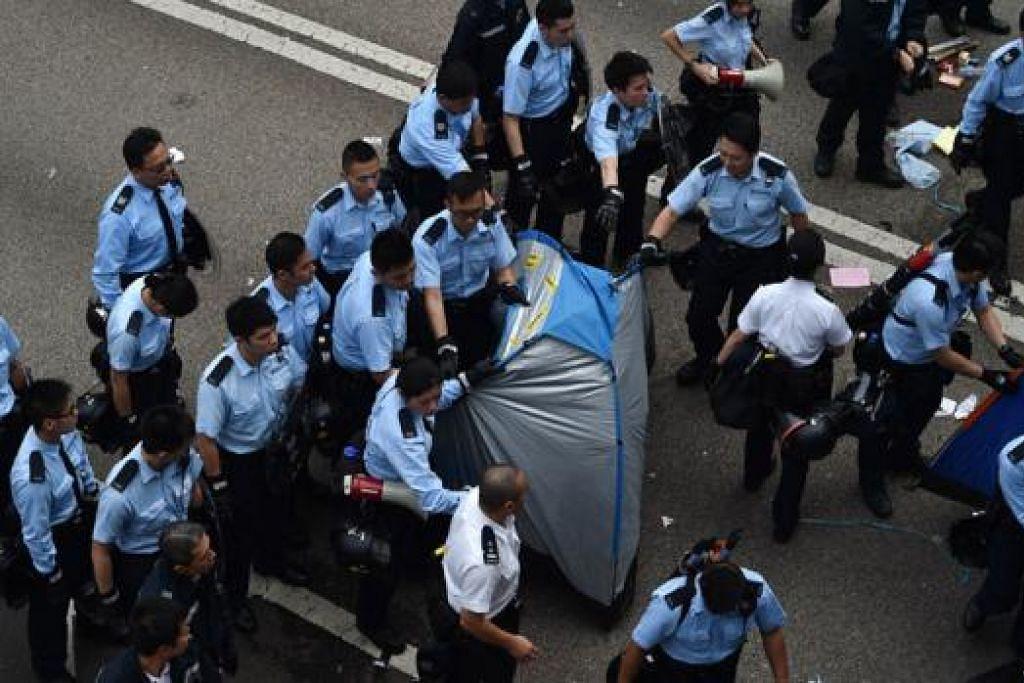 AMBIL TINDAKAN: Polis Hongkong mula mengalihkan khemah penunjuk perasaan di daerah Admilralty, semalam. - Foto AFP
