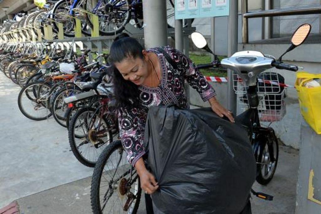 BERBASIKAL DARI RUMAH KE STESEN MRT: Cik Lina Rahim menunggang basikal dari rumahnya di Joo Chiat Complex ke stesen MRT Eunos sebelum meneruskan perjalanan beliau ke tempat kerja dengan menaiki MRT. - Foto M.O. SALLEH