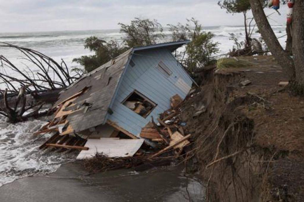 KESAN CUACA BURUK: Sebuah rumah hampir roboh di Washaway Beach, Washington, semalam selepas taufan melanda barat Amerika Syarikat. Taufan yang sama turut melanda utara dan tengah California. - Foto REUTERS