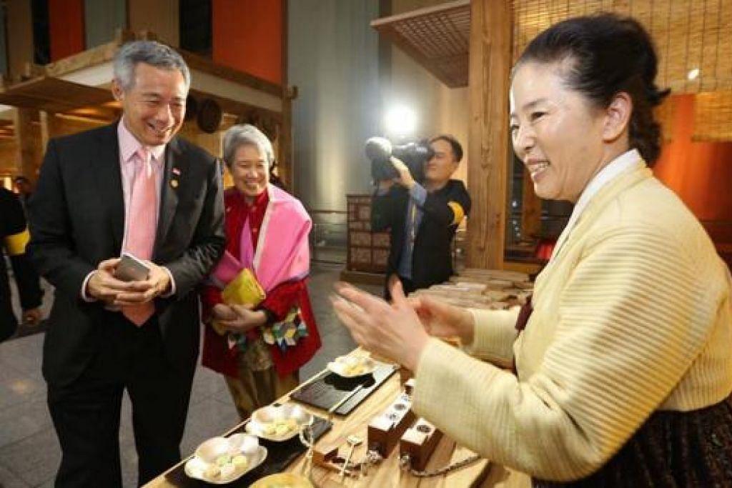 BELAJAR TRADISI KOREA: Encik Lee bersama isterinya, Cik Ho Ching, belajar tentang membuat rice cakes dan seni tradisi Korea sebelum menghadiri majlis makan malam Sidang Puncak Peringatan Asean-Republik Korea (ROK).