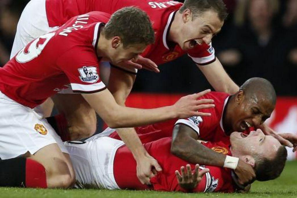 TERLALU GAGAH: Wayne Rooney (berbaring) dikerumuni rakan sepasukan selepas menjaringkan gol pertama perlawanan di Old Trafford.