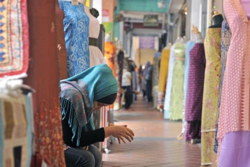 PELANGGAN TIDAK BERKUNJUNG JUA: Seorang peniaga menunduk sambil menanti kedatangan pelanggan di Arab Street baru-baru ini.