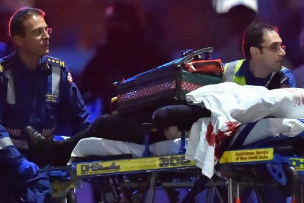MANGSA PENGGANAS: Kakitangan perubatan mengusung keluar mayat salah seorang tebusan yang terkorban dalam serbuan polis ke atas kafe Lindt kelmarin.
