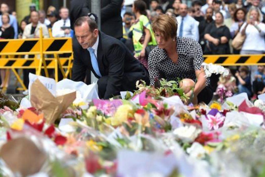 BERI PENGHORMATAN: Perdana Menteri Australia, Encik Tony Abbott, dan isterinya Cik Margaret meletakkan jambangan bunga di lokasi insiden tebusan berdarah di Sydney, kelmarin. - Foto AFP