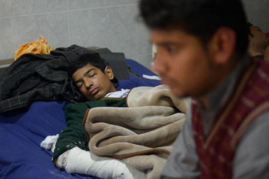 YANG TERSELAMAT: Seorang pelajar, Mehran (kiri), sedang berehat di hospital bersama seorang lagi temannya selepas sekolahnya di Peshawar diserang kumpulan Taleban kelmarin. - Foto AFP