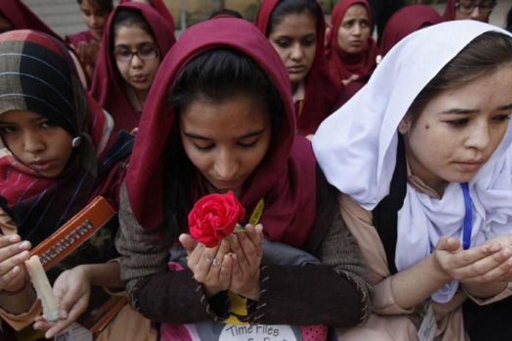 MEMPERINGATI MANGSA: Pelajar di sebuah sekolah di Karachi berdoa untuk mangsa serangan Taleban di Sekolah Awam Tentera di Peshawar, Pakistan, semalam. Sekurang-kurangnya 132 pelajar dan sembilan kakitangan terbunuh apabila lelaki bersenjata memecah masuk sekolah itu dan melepaskan tembakan. - Foto REUTERS