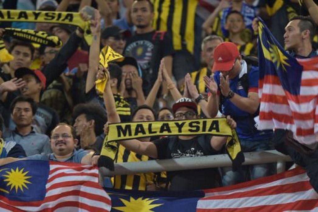HARIMAU MALAYA: Walaupun tewas di tangan Thailand, penyokong Malaysia tidak putus asa memberi sokongan lantang kepada pasukan mereka di Stadium Rajamangala, Bangkok. - Foto AFP