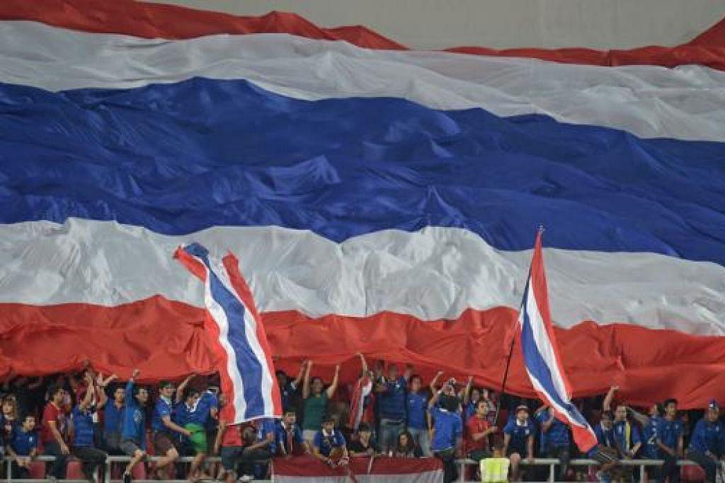 GAJAH PERANG: Penyokong pasukan 'Gajah Perang' mengibarkan bendera gergasi sebagai meraikan kemenangan Thailand di Stadium Rajamangala kelmarin. - Foto AFP