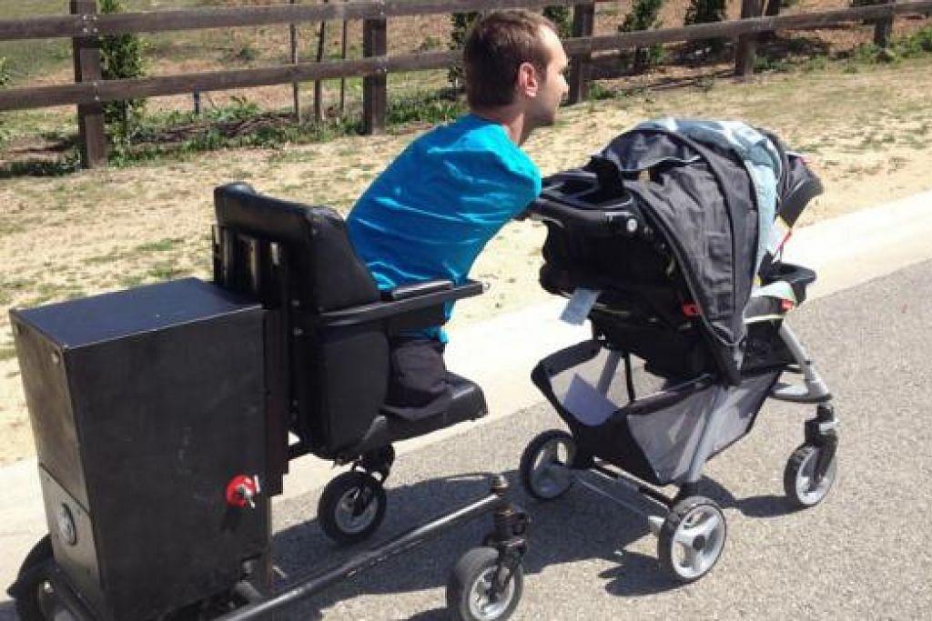 BERSAMA ANAK KESAYANGAN: Encik Nick Vujicic menggunakan kerusi roda khas sedang menolak kereta tolak anaknya menggunakan tubuhnya.- Foto LIFE WITHOUT LIMBS