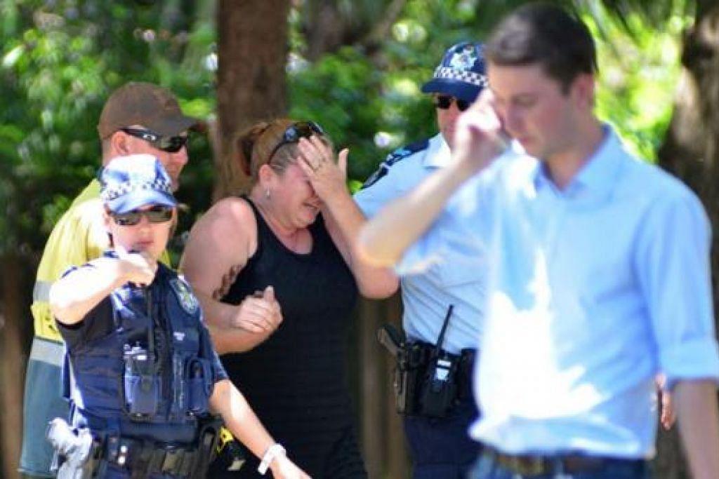 MENYAYAT HATI: Seorang wanita terpaksa dipujuk polis selepas melihat lokasi tragedi pembunuhan beramai-ramai di Cairns. - Foto AFP
