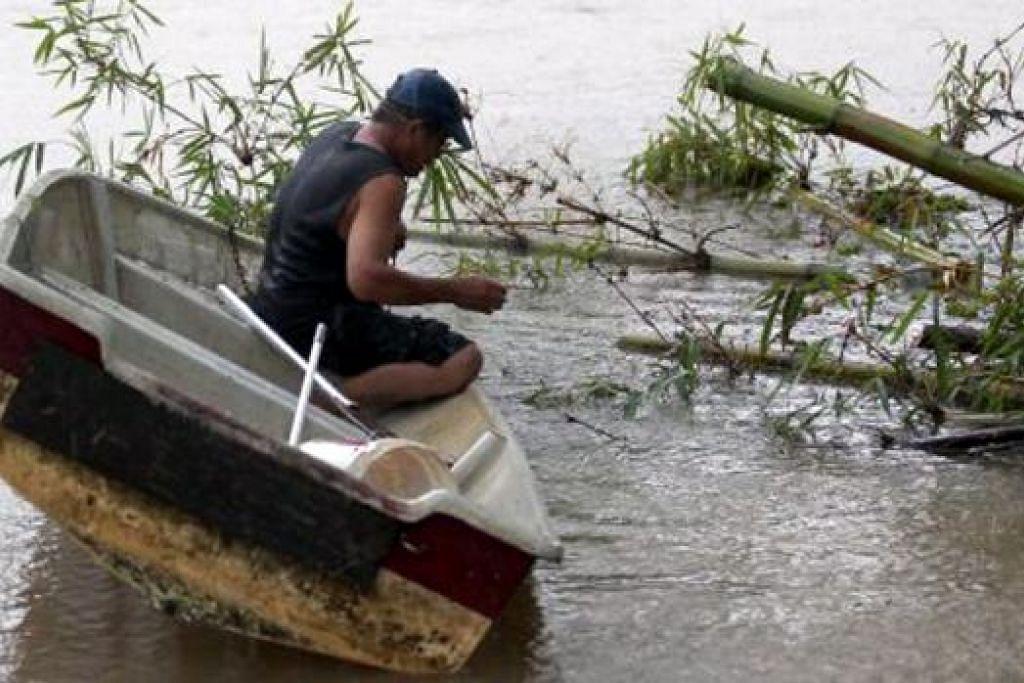 BERI LALUAN: Penduduk di Kampung Repek memotong pokok buluh yang menghalang laluan air yang boleh menyebabkan banjir berdekatan rumahnya. - Foto BHM
