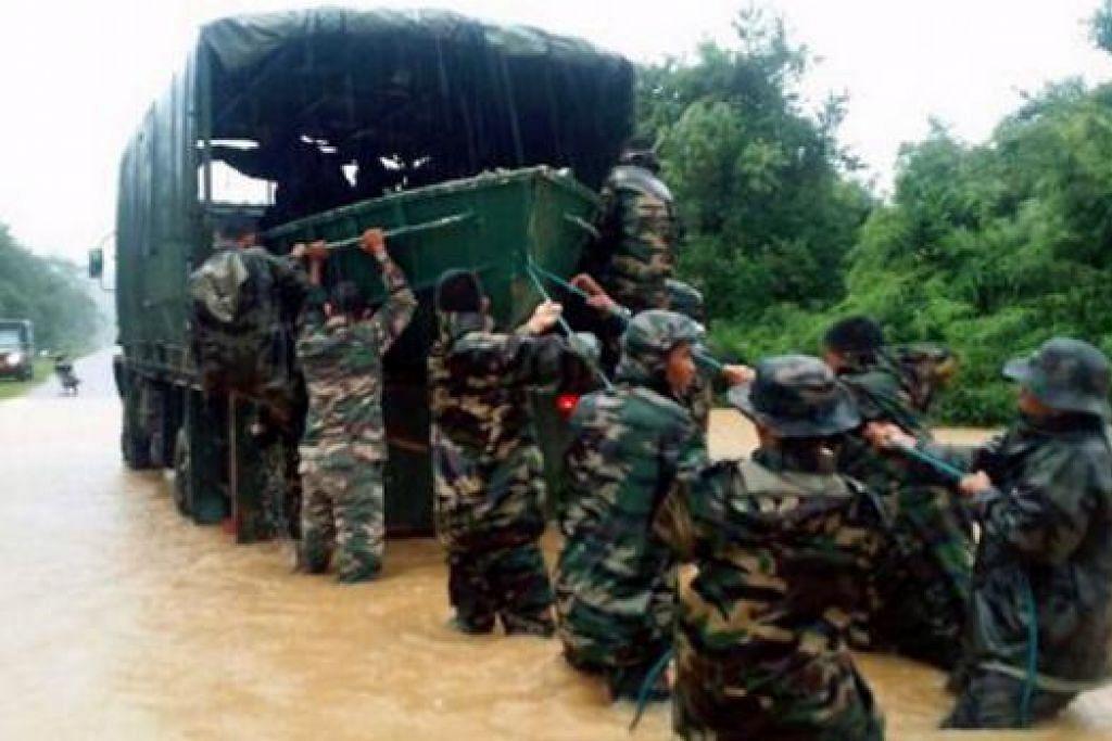 ASKAR TURUT MEMBANTU: Rejimen Askar Melayu di Raja menurunkan bot untuk memberi bantuan kepada mangsa banjir di Kampung Minda Talong. - Foto BHM