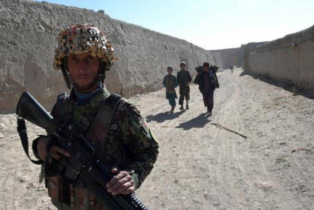 DI SINI BERMULA TALEBAN: Dalam foto yang dipetik 11 Disember lalu ini, kelihatan seorang askar Afghanistan sedang meronda pekarangan masjid di mana Mullah Omar menubuhkan gerakan Taleban 20 tahun lalu di Sangesar. - Foto AFP