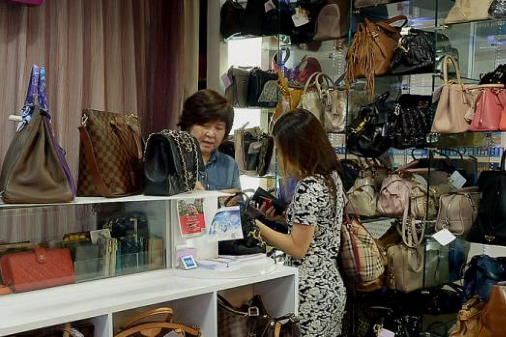 DAPAT SAMBUTAN: Seorang pekerja kedai Madam Milan (kiri) melayan pelanggan di kedainya yang menjual dan membeli beg mewah terpakai. - Foto TUKIMAN WARJI