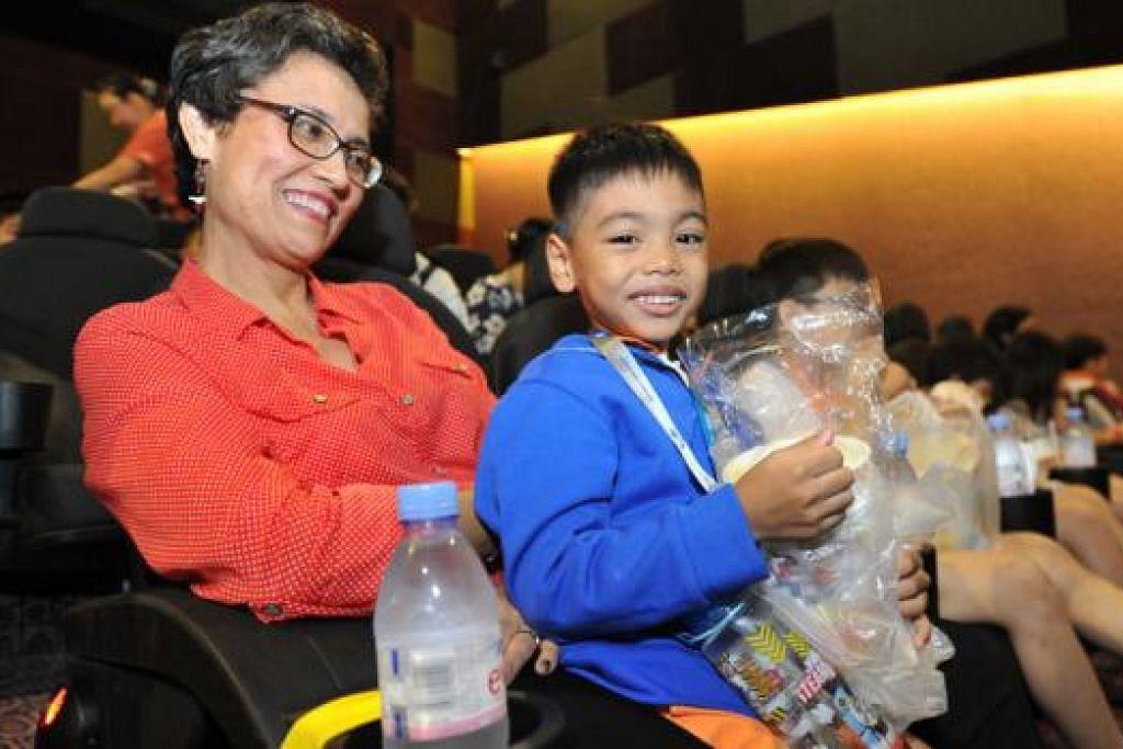 TONTON WAYANG: Guru badan amal Child @ St 11, Cik Jacqueline Fletcher, bersama Muhd Fazil, lima tahun, di acara Tayangan Filem Amal SPH, Khamis lalu. - Foto SPH