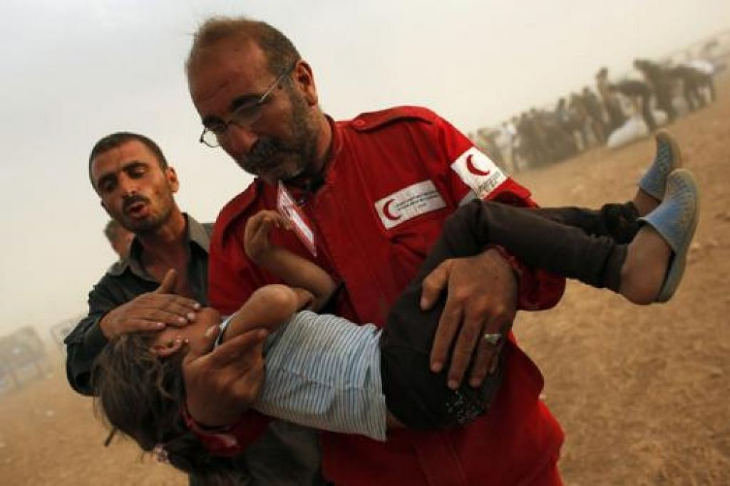 HULUR BANTUAN: Anggota Syrian Arab Red Crescent sedang mengangkat pelarian kanak-kanak Kurd Syria pergi ke khemah bantuan kecemasan. Mereka baru sahaja menembusi sempadan Turkey dan Syria, dekat kawasan Suruc, wilayah Sanliurfa, September lalu.