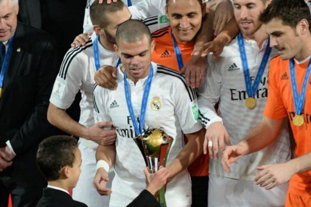 SANG JUARA: Putera Hassan III bagi Maghribi menyampaikan trofi kejuaraan kepada para pemain Real Madrid. - Foto AFP