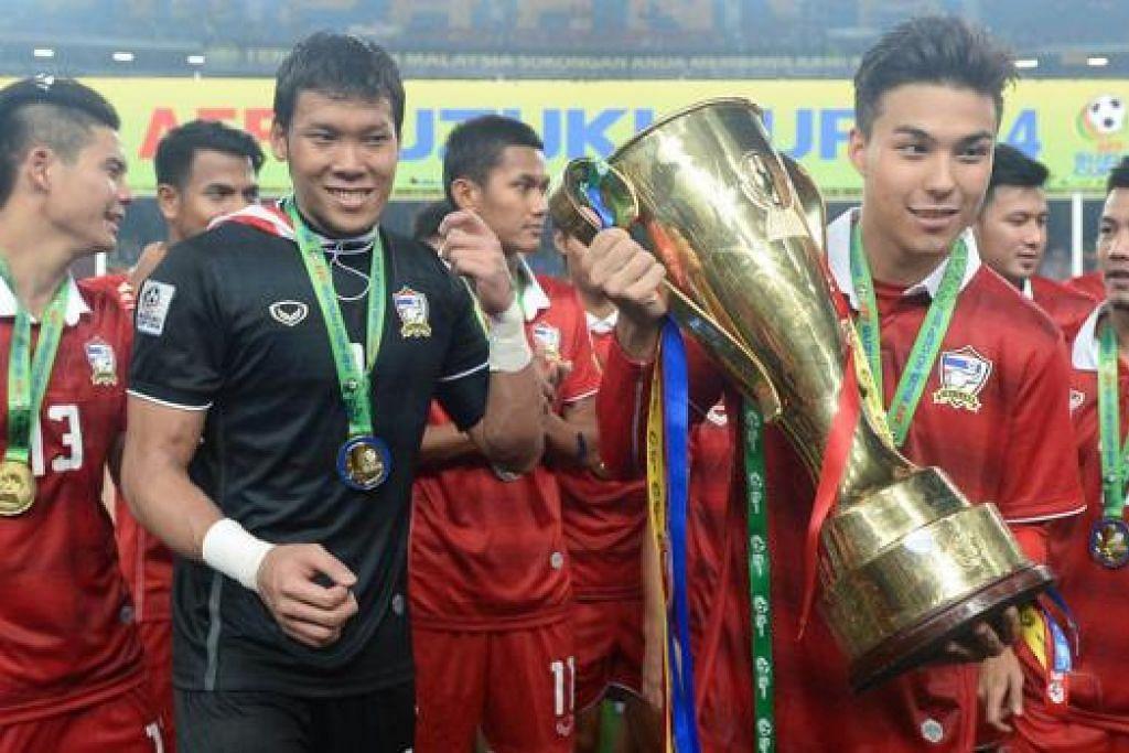 TROFI KEMEGAHAN: Bintang muda Thailand, Charyl Chappuis, membawa mahkota kejuaraan Piala AFF Suzuki, selepas final kedua di Stadium Bukit Jalil, Malaysia, kelmarin. Thai atasi Malaysia dengan kemenangan agregat 4-3. - Foto AFP
