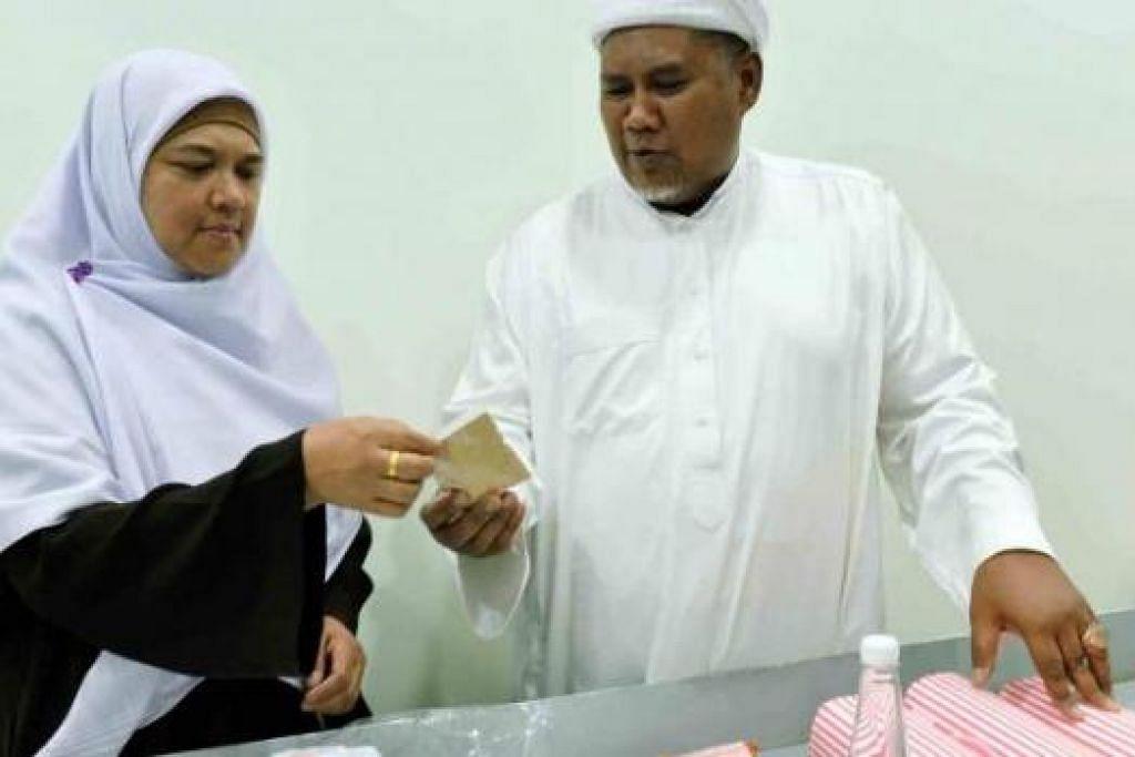 PASTIKAN YANG TERBAIK: Haji Mohd Roslan dan isteri, Cik Masirah Yusof Ibrahim berganding bahu mengelolakan syarikat Pengurusan Jenazah Sinaran Baharu. - Foto-foto KHALID BABA