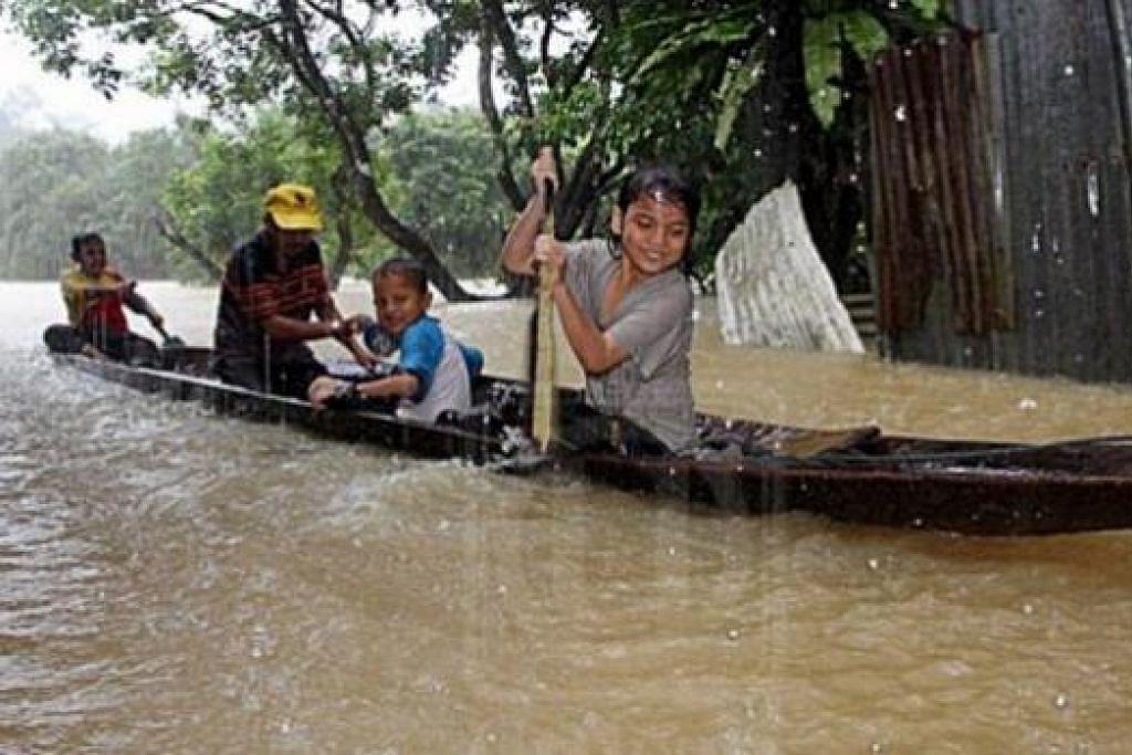 MENCARI TEMPAT SELAMAT: Mangsa banjir, Encik Mat Ali Ibrahim, bersama anak-anaknya mengharungi banjir menggunakan sampan di Kampung Pinang Baru, Dungun di Terengganu. - Foto UTUSAN MELAYU