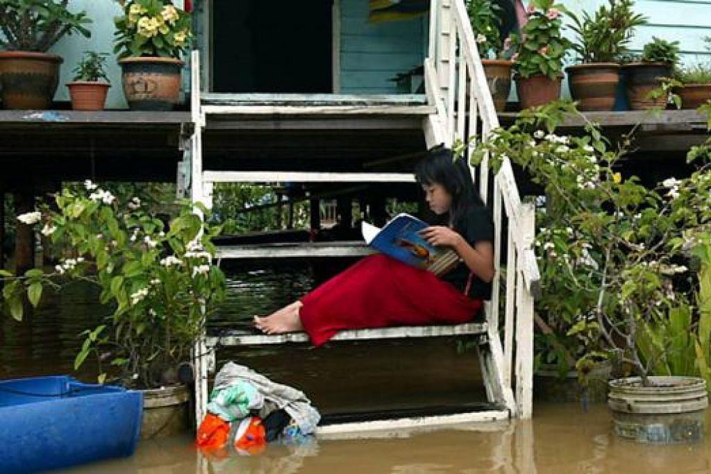 REHAT: Gadis ini menghabiskan masa membaca buku di tangga rumahnya yang ditenggelami air di Kampung Pulau keladi, Pekan, Pahang. - Foto The STAR
